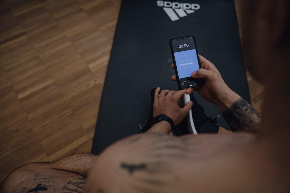 Uomo sceglie allenamento sullo smartphone
