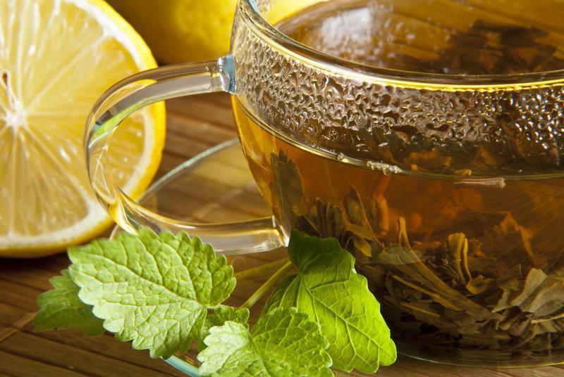 Gros plan sur une tasse de thé vert avec des feuilles de menthe et des rondelles de citron.