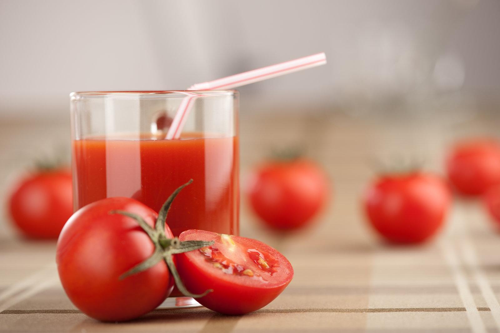 Gros plan sur un verrre de jus de tomate et des tomates cerises.