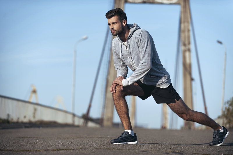 Important stretching. Full length of handsome young man stretching his body before running while standing on the bridge