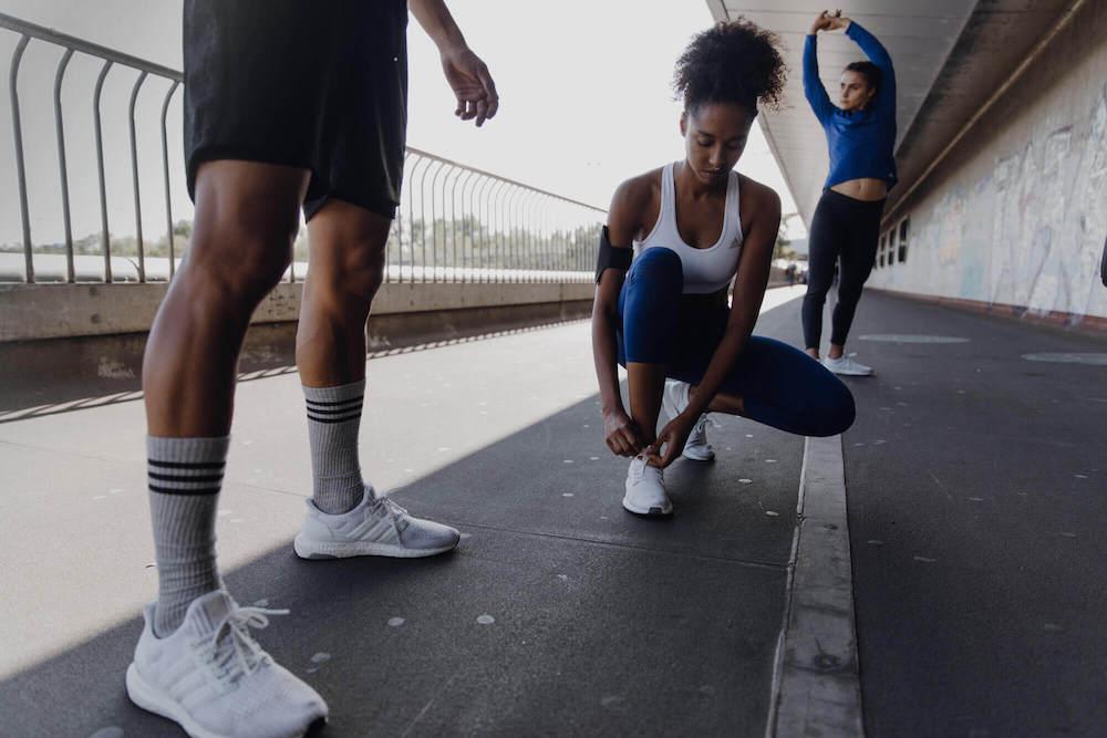Eine junge Frau bindet sich die Schuhbänder ihrer Laufschuhe