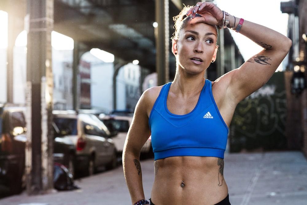 Eine Frau in adidas-Sportkleidung macht während des Laufs eine Pause
