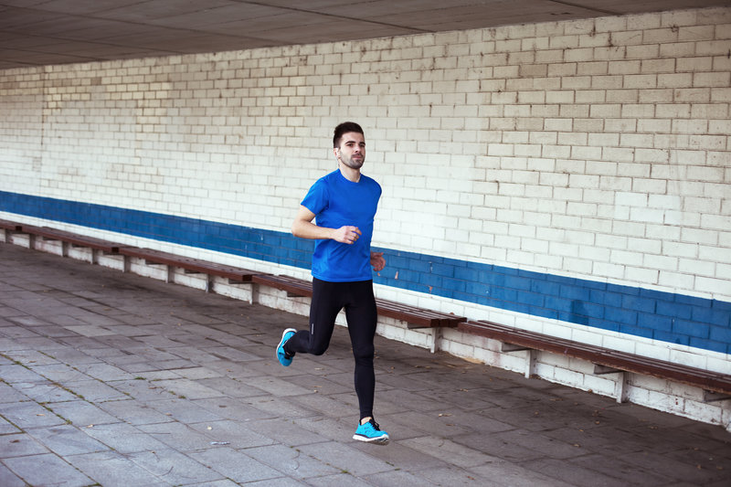 young and handsome athlete with earphones running outdoors (with little motion blur)