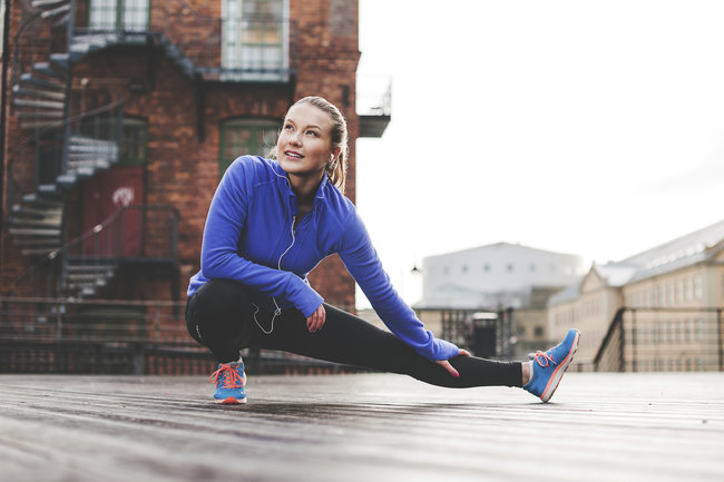 A girl is stretching in an outfit for running.