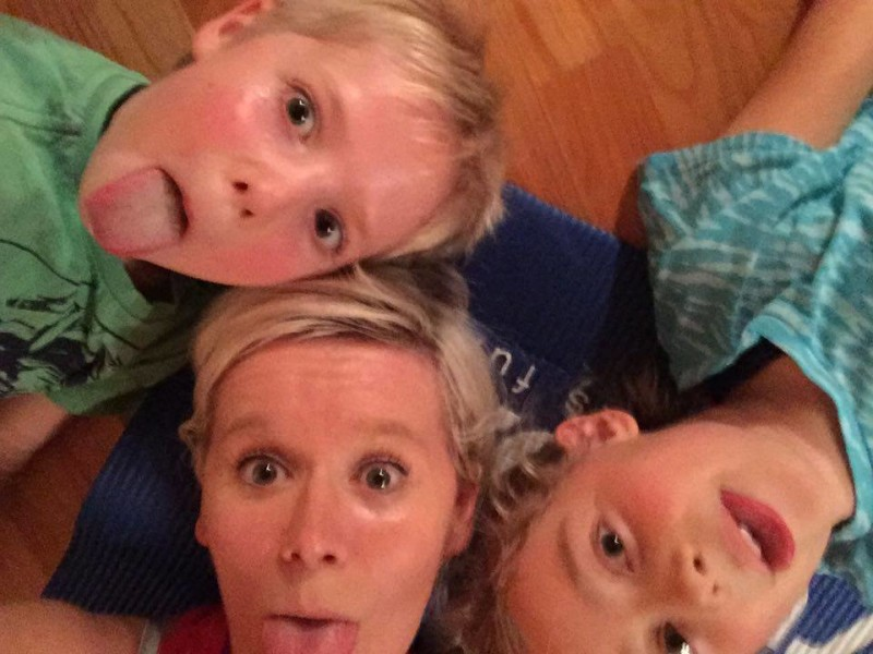 A mother and her two kids are lying on the floor