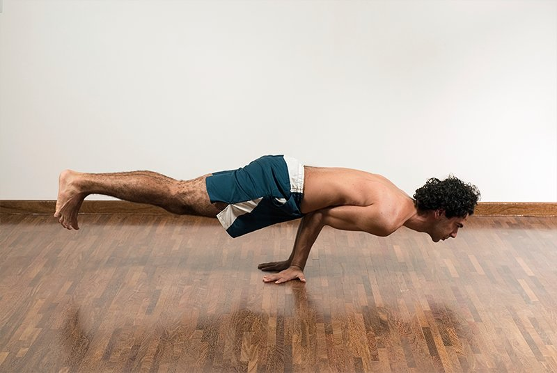 man doing a difficult yoga pose on the floor