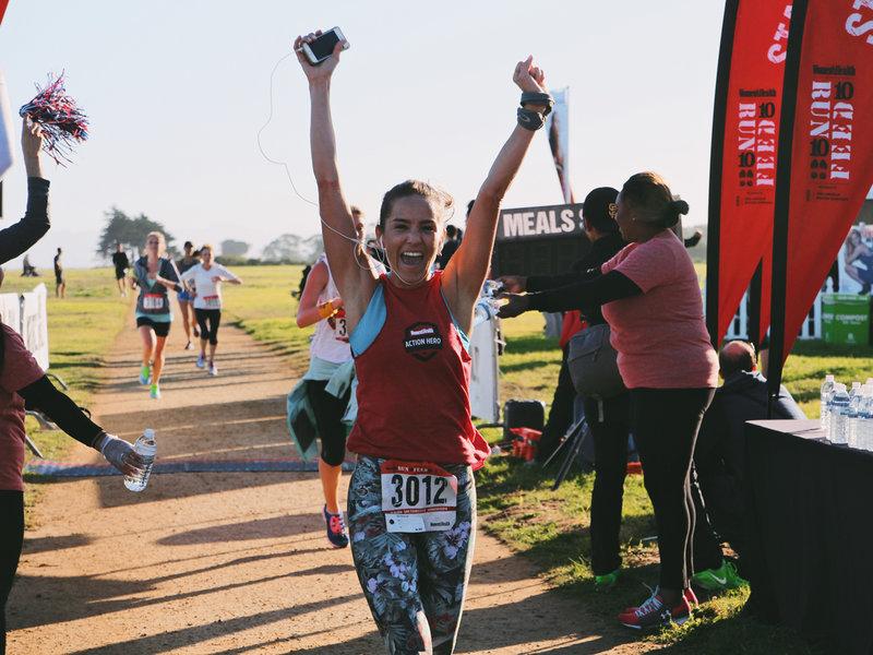 Female runner celebrating her victory on the finish line.