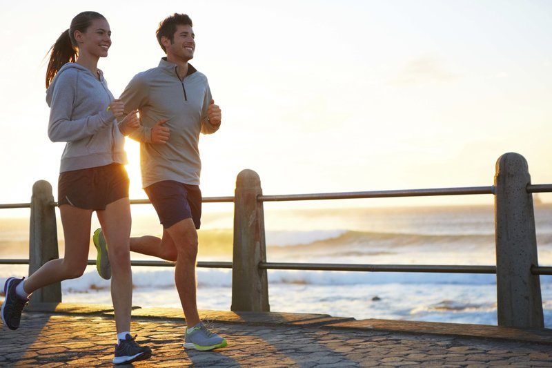 A young couple jogging on the promenade at sunset.