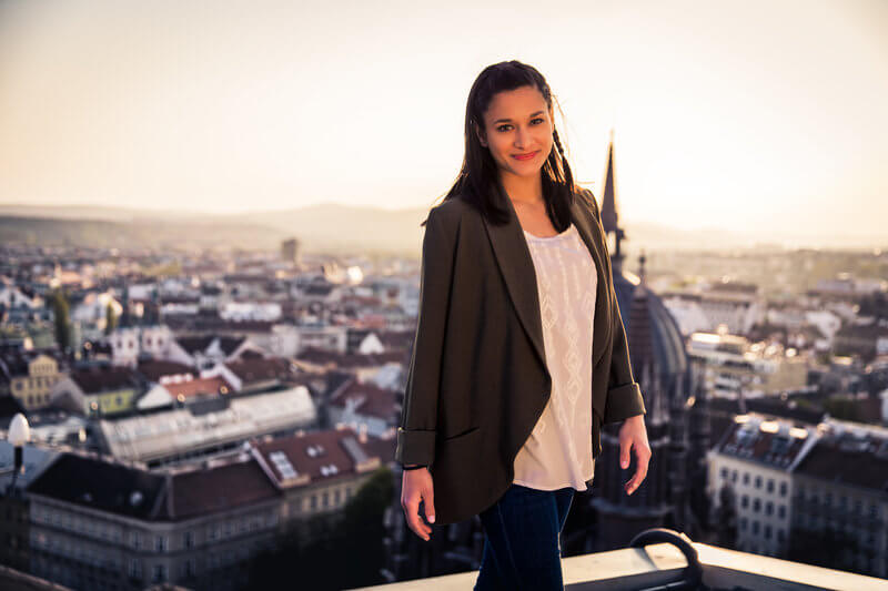 Photo of Pam Foster. A young, attractive woman with brown hair. She is standing on a roof terrace, behind her the city while sunset.