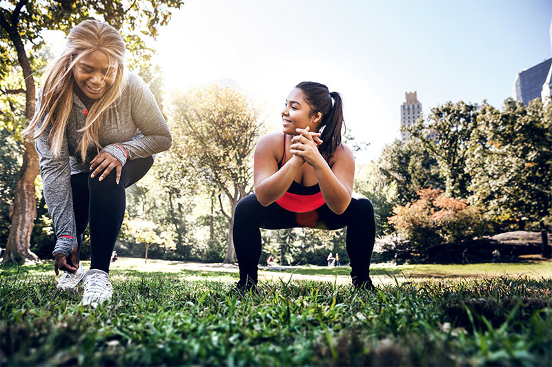 Two corpulent women are doing workouts together in the park.