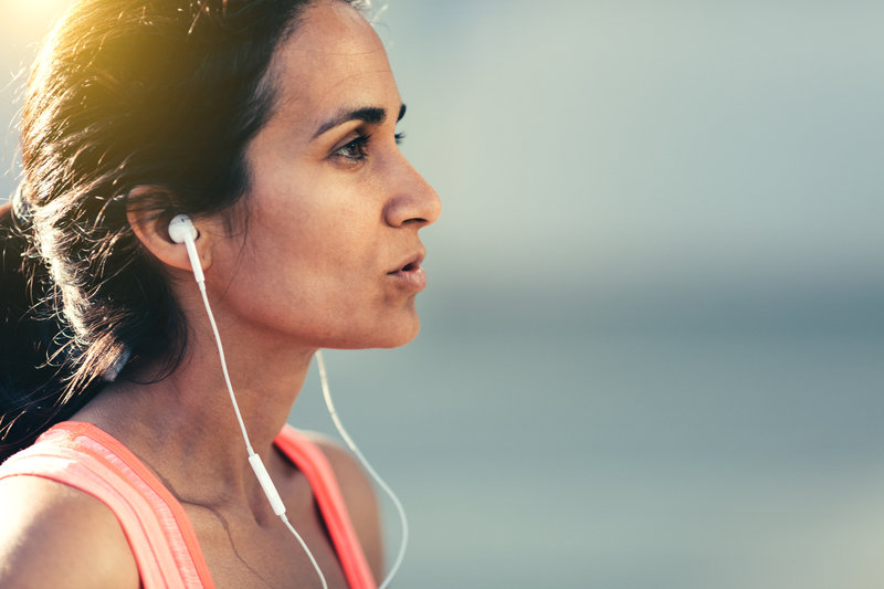 Young woman running and listening music