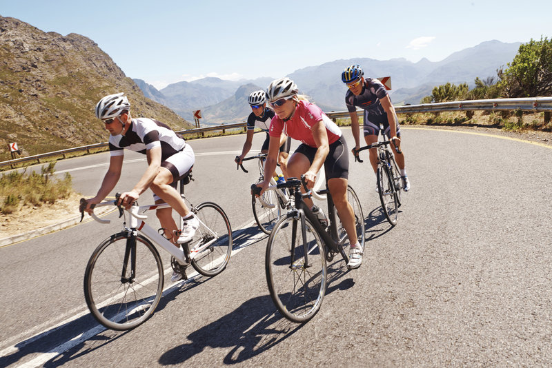 Shot of a group of cyclists riding up a gently sloping country road