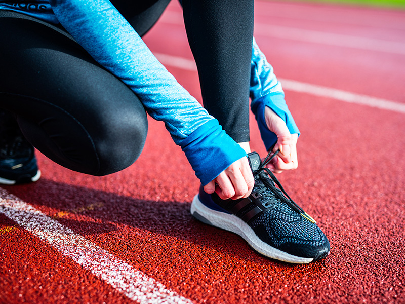 close up of a young woman tying her running shoe.