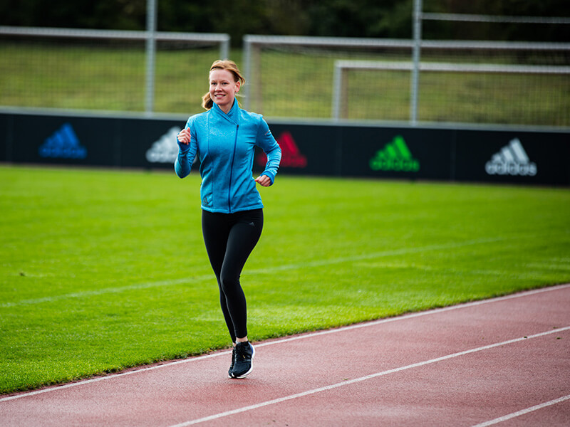 Young woman running on a running track.