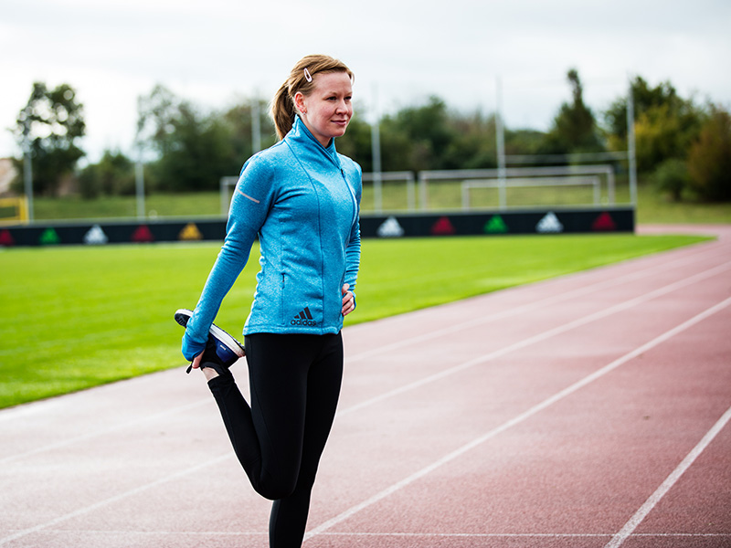 Young woman stretching her leg on a running track.