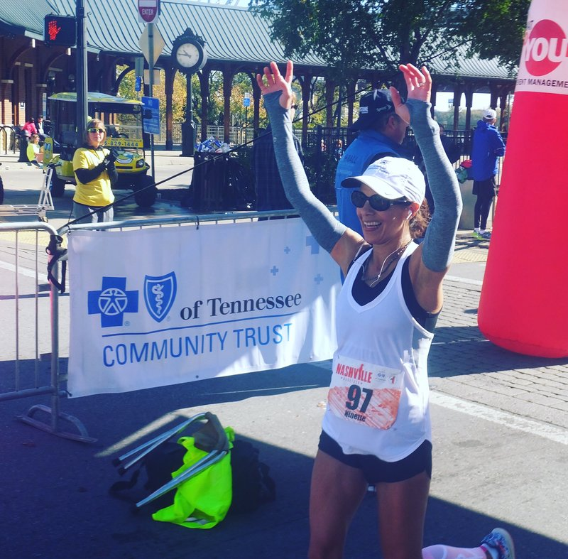 A woman runs through the finish line