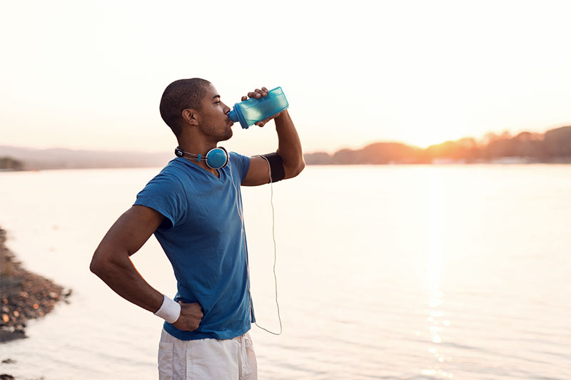 Young man is drinking from his water bottler after his run.