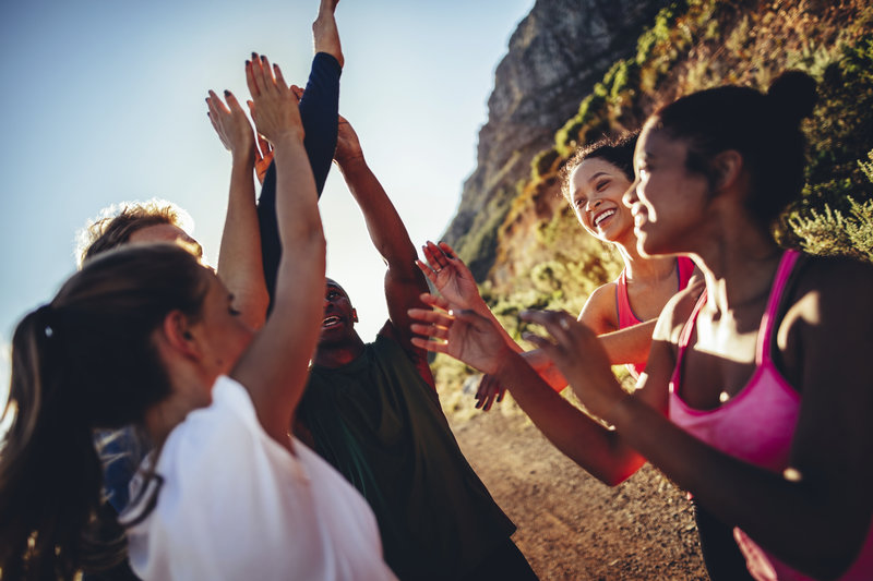 Multi-ethnical group of young adult runners cheering and high fiving after a good run outdoors