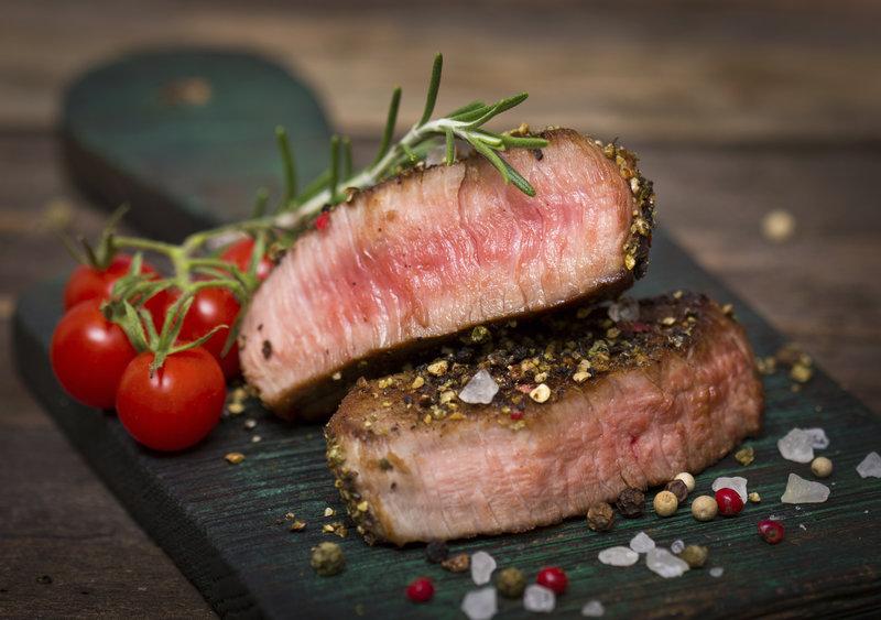 Nahaufnahme von einem saftigen Steak auf einer Steinplatte.