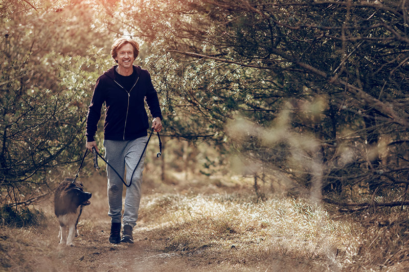 A man is running in the forrest with his dog