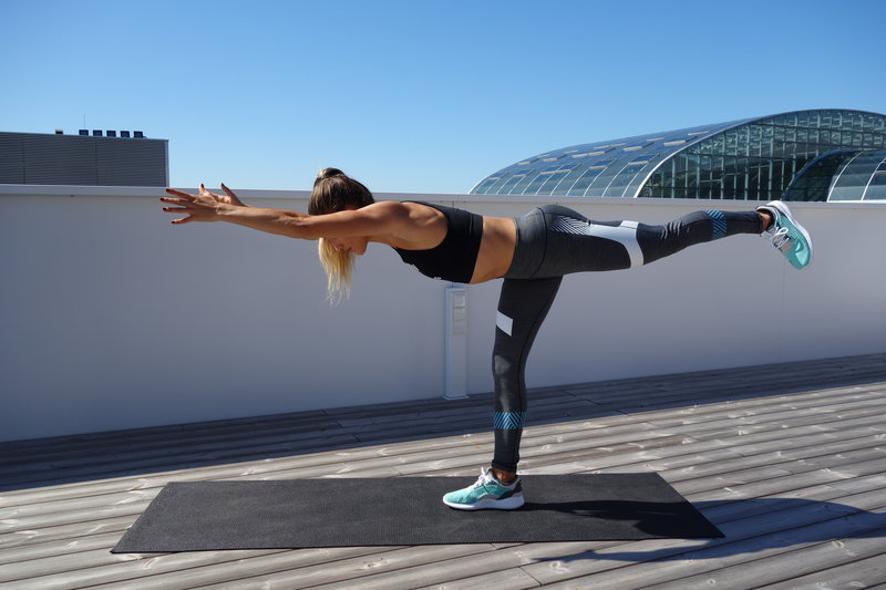 A young woman is doing Warrior three hamstring extensions with leg lifts