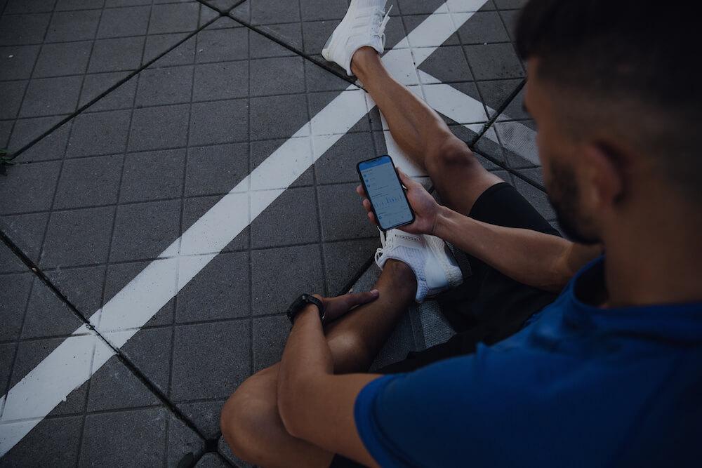 Um corredor verificando o progresso da corrida no app Runtastic