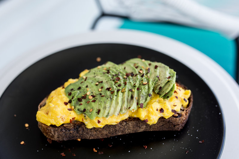 Avocadobread with scrambled eggs on a plate