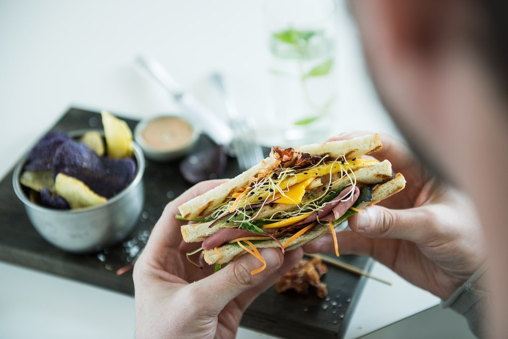 un hombre comiendo un sandwich