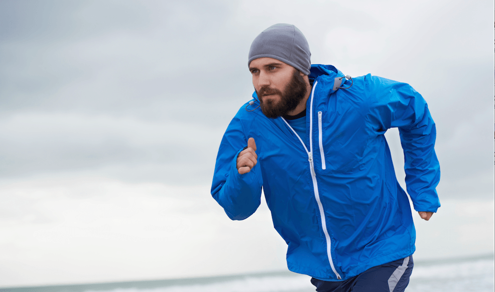 A man is running in a running-jacket.