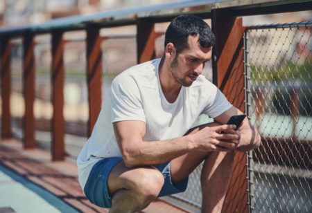 Man looking at his phone before working out