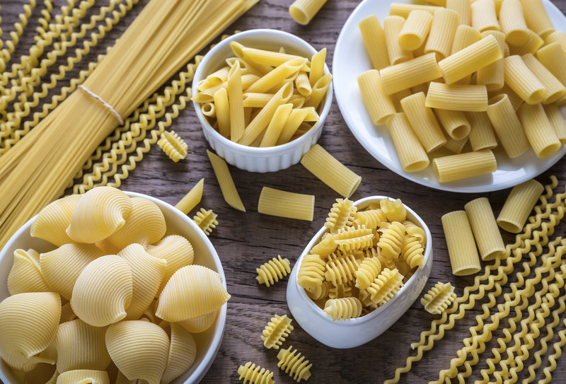 Various types of pasta on the wooden background