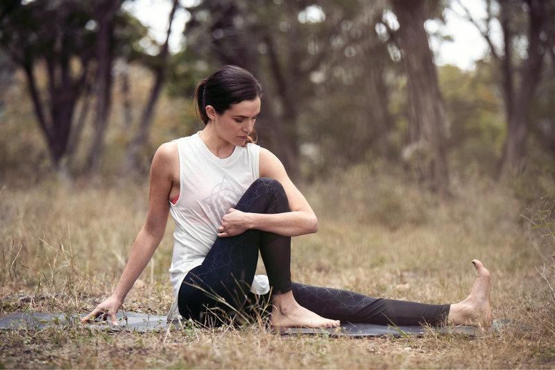 Frau macht Yoga auf einer Wiese