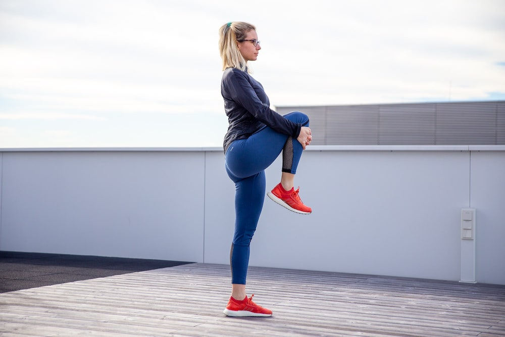 une femme fait un étirement genou-poitrine