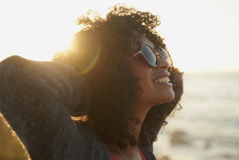 Belle jeune femme profitant du coucher de soleil.