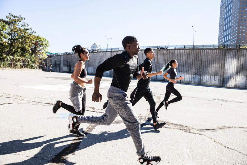 Groupe de jeunes gens effectuant un sprint.