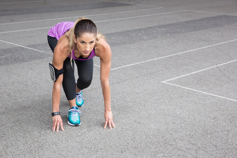 Young woman in starting position for a sprint.