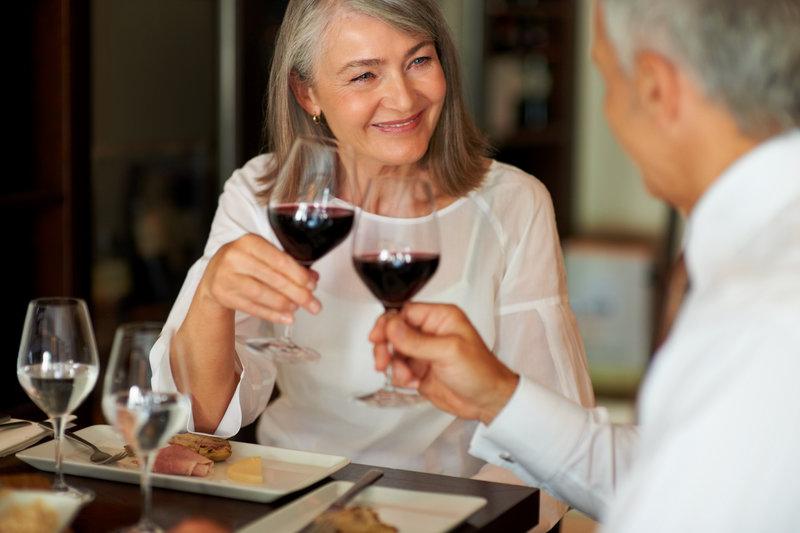 Couple en train de trinquer avec un verre de vin rouge.