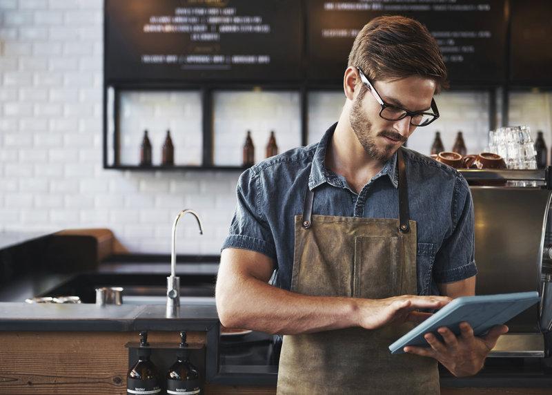 Jeune barista dans un café qui regarde quelque chose sur sa tablette.