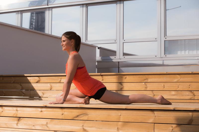 Jeune femme faisant du yoga sur une terrasse