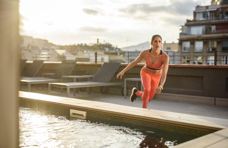 Jeune femme qui s'entraîne près d'une piscine