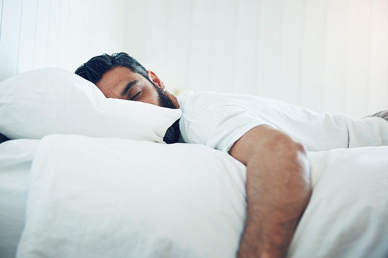 Un homme qui dort sur le ventre