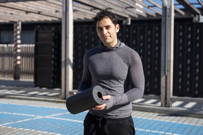Ein Mann in Sportkleidung mit einer Blackroll
