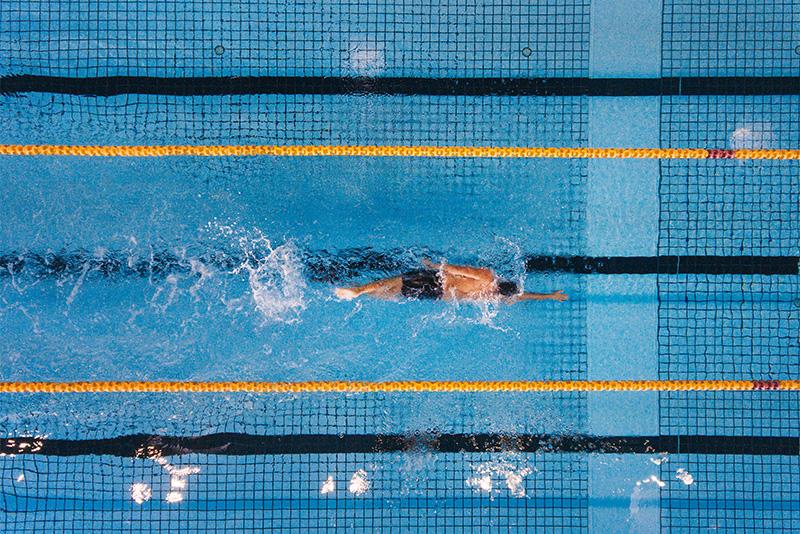 EIn Mann schwimmt Längen im Schwimmbecken