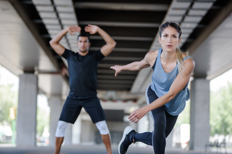A woman and a man working out outside