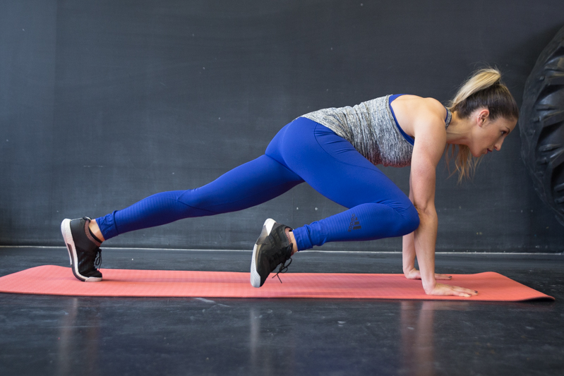 A woman is doing a commander push-up