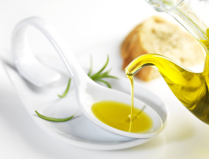 Virgin olive oil pouring in a spoon