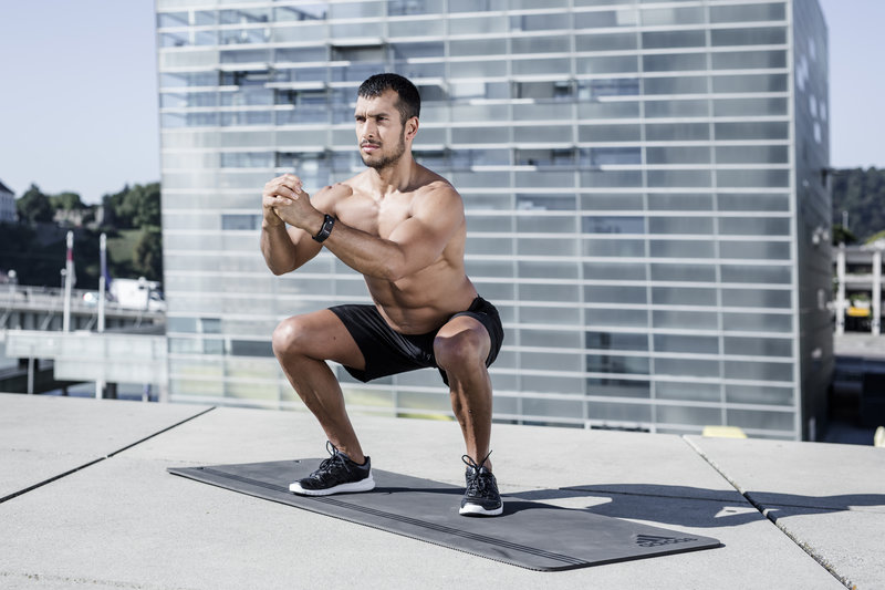 Athletic man doing squats outside.