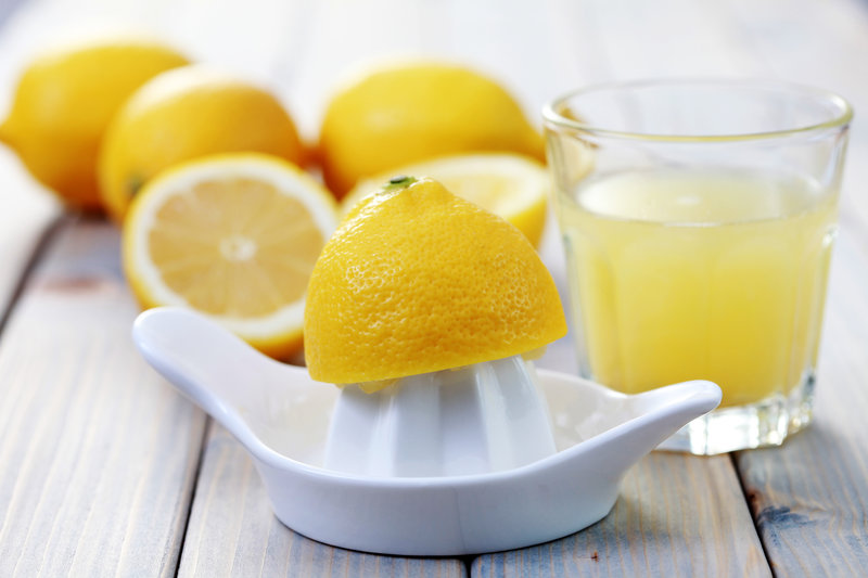Foto von einer Zitrone auf einer Saftpresse, neben einem Glas Zitronensaft