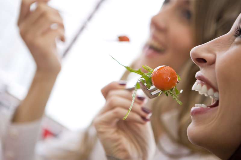 Zwei Freundinnen essen einen gemischten Salat.