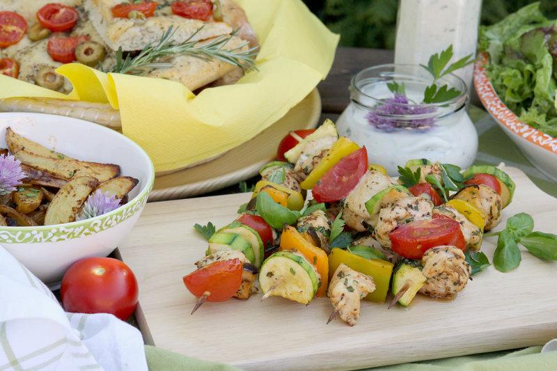 Mediterrane Gemüse-Hühner-Spieße mit Bratkartoffeln und Focaccia im Hintergrund.